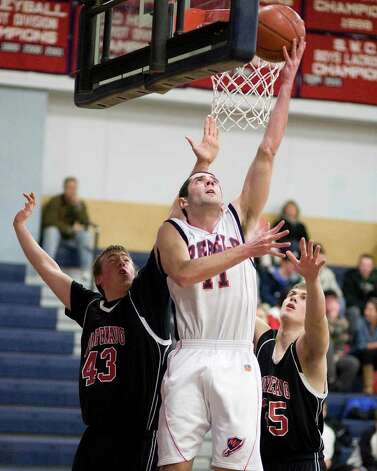New Fairfield's Billy Kimmel puts up a reverse layup between Pomperaug defenders Kevin Foy (43) and Tim Harris Thursday night at New Fairfield High School. Photo: Barry Horn