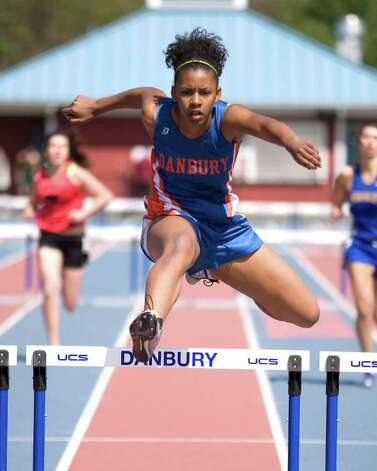 Danbury's Nyoshee Lowry easily wins her heat in the 300 intermediate hurdles at the O'Grady Relays Saturday at Danbury High School. Photo: Barry Horn
