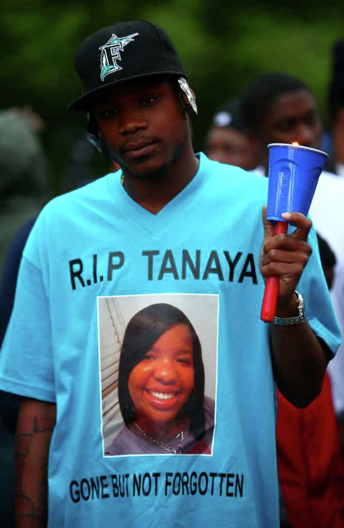 Aufu Snow wears a shirt memorializing Tanaya Gilbert, a 19 year-old woman shot and killed in South Seattle. A vigil was held for the woman, who was pregnant, on Thursday, July 14, 2011 on 54th Avenue South, site of the shooting. More shots were fired as the vigil was winding down. Police said someone fired on a blue and silver Dodge Magnum with chrome wheels. The car sped off after the shooting.