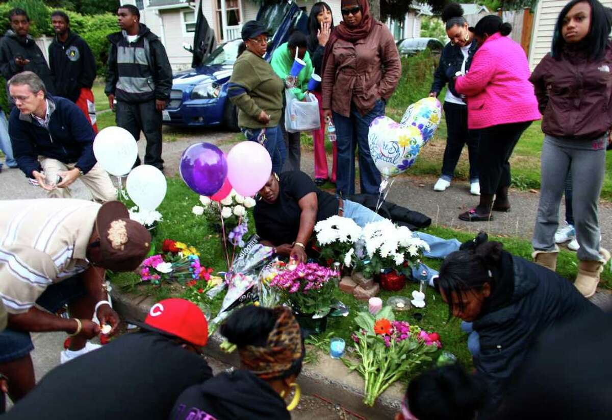 Mourners arrange candles and flowers during a memorial for Tanaya Gilbert, a 19 year-old woman shot and killed in South Seattle. A memorial was held for the woman, who was pregnant.