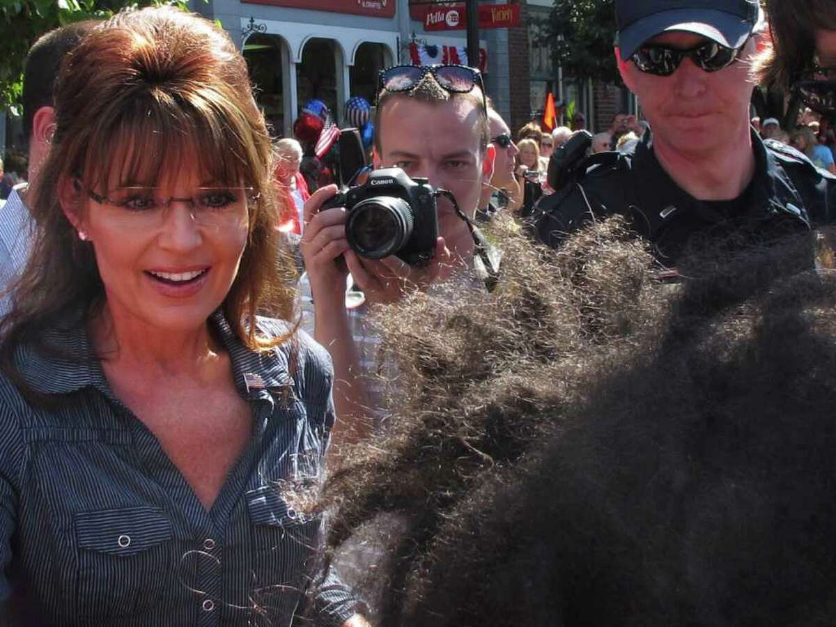 Former Alaska Gov. Sarah Palin, left, greets a child in downtown Pella, Iowa on Tuesday, June 28, 2011, before attending the first public screening of
