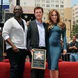 Randy Jackson (L) and singer/actress Jennifer Lopez, stand beside producer Simon Fuller (C) after he unveilled it at the ceremony honoring him with a Hollywood Walk of Fame star, held in Hollywood, California on May 23, 2011        AFP PHOTO/Mark RALSTON (Photo credit should read MARK RALSTON/AFP/Getty Images)