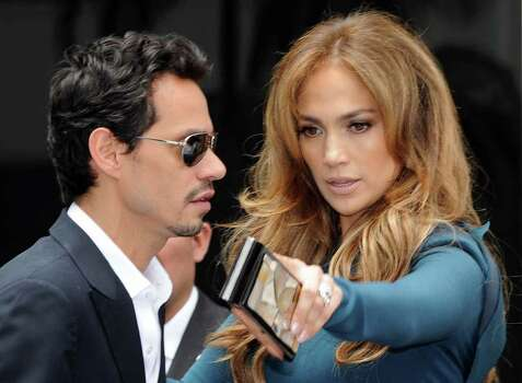 Singer Mark Anthony and his wife singer/actress Jennifer Lopez look on as producer Simon Fuller unveils his star at the ceremony honoring him with a Hollywood Walk of Fame star, held in Hollywood, California on May 23, 2011        AFP PHOTO/Mark RALSTON (Photo credit should read MARK RALSTON/AFP/Getty Images) Photo: MARK RALSTON, Staff / AFP