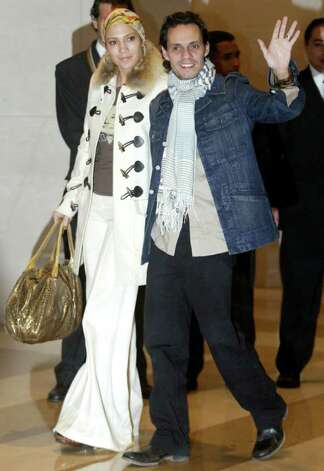 Artists Jennifer Lopez (L) and Marc Anthony greet fans as they arrive at a hotel in Lima December 1, 2005. Photo: EL COMERCIO, AP