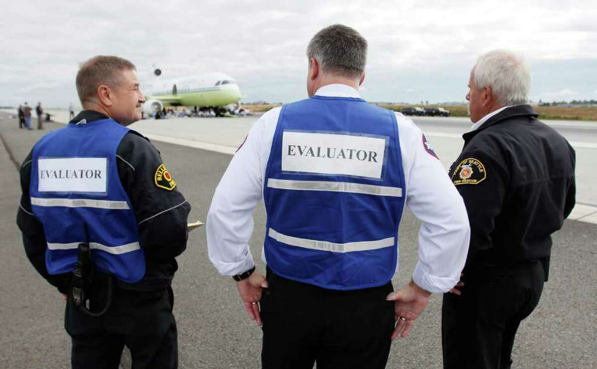Evaluators assess the performance of fire and rescue teams during a training exercise at Sea-Tac International Airport.