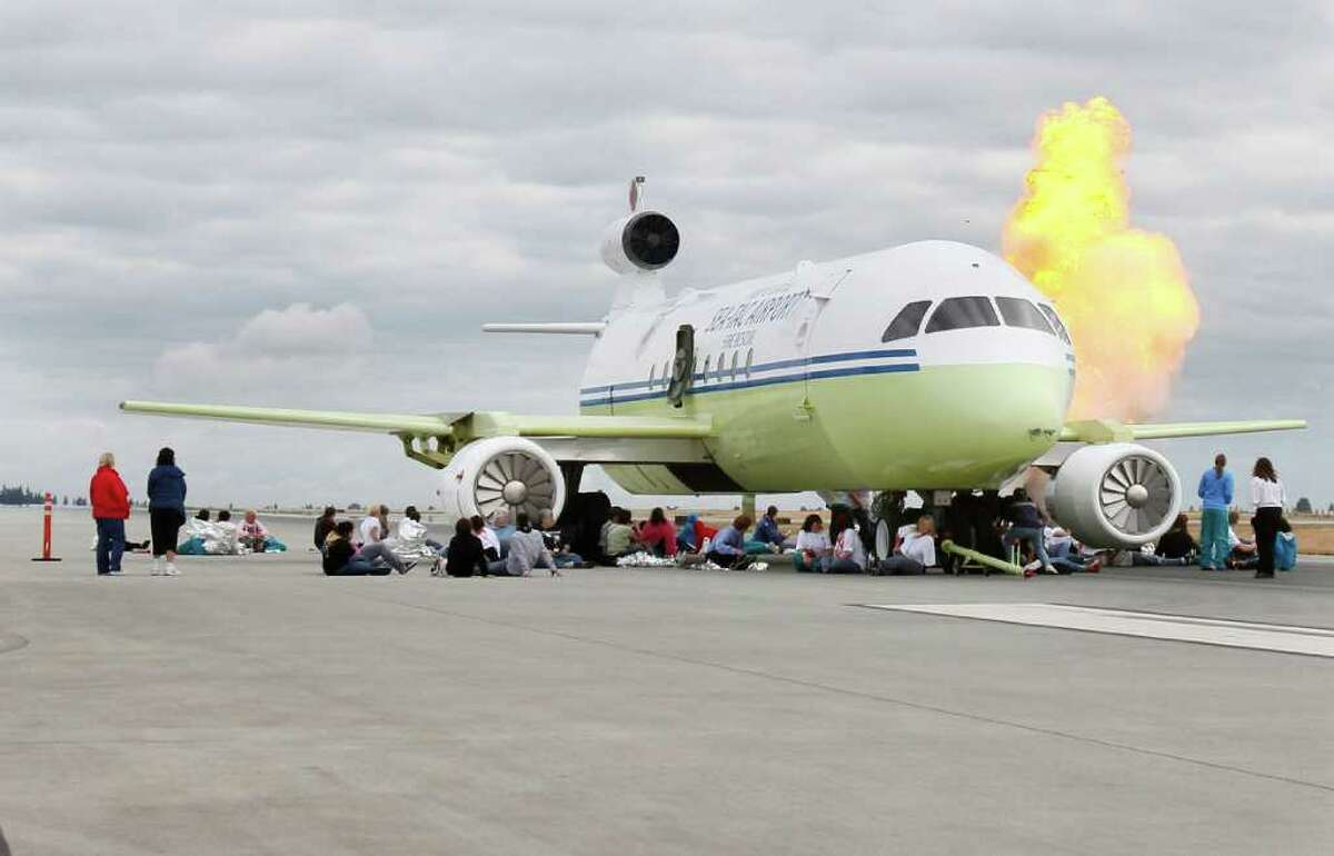 A 'flour bomb' explodes during a fire and rescue training scenario at Sea-Tac International Airport in on July 15, 2011. The drill involved a mock aircraft and over 100 volunteers playing the role of victims. Once scenario involved a hostage situation and one involved a simulated bomb explosion.