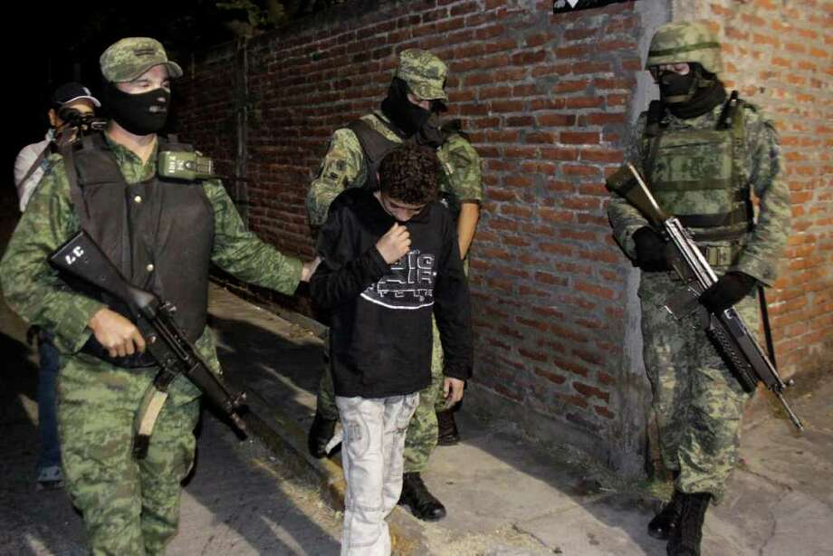 "Soldiers escort a 14-year-old known as ""El Ponchis"" who is suspected of working as a killer for a drug cartel, in the city of Cuernavaca, Mexico, Friday Dec. 3, 2010. The youth, who was captured late Thursday at the airport in Cuernavaca with his 16-year-old sister as they were trying to catch a flight to Tijuana and flee the country to San Diego, is accused of participating in four beheadings for a Mexican drug cartel and will be tried under a state juvenile law and will receive only three years in prison if convicted, a judge said Sunday. (AP Photo/Antonio Sierra) Photo: Antonio Sierra, STR / AP"