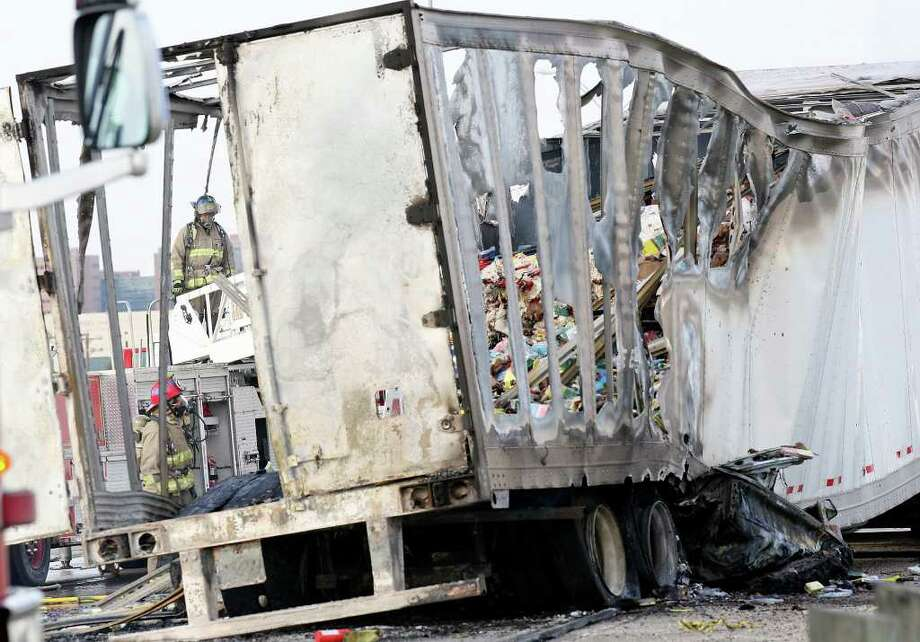 Firefighters work the scene of an 18-wheel tractor-trailer fire after a vehicle became caught under the 18-wheeler on I-35 North at the AT&T Center Parkway exit Friday. The female driver of the vehicle was killed. Photo: EDWARD A. ORNELAS, Edward A. Ornelas/Express-News / © SAN ANTONIO EXPRESS-NEWS (NFS)