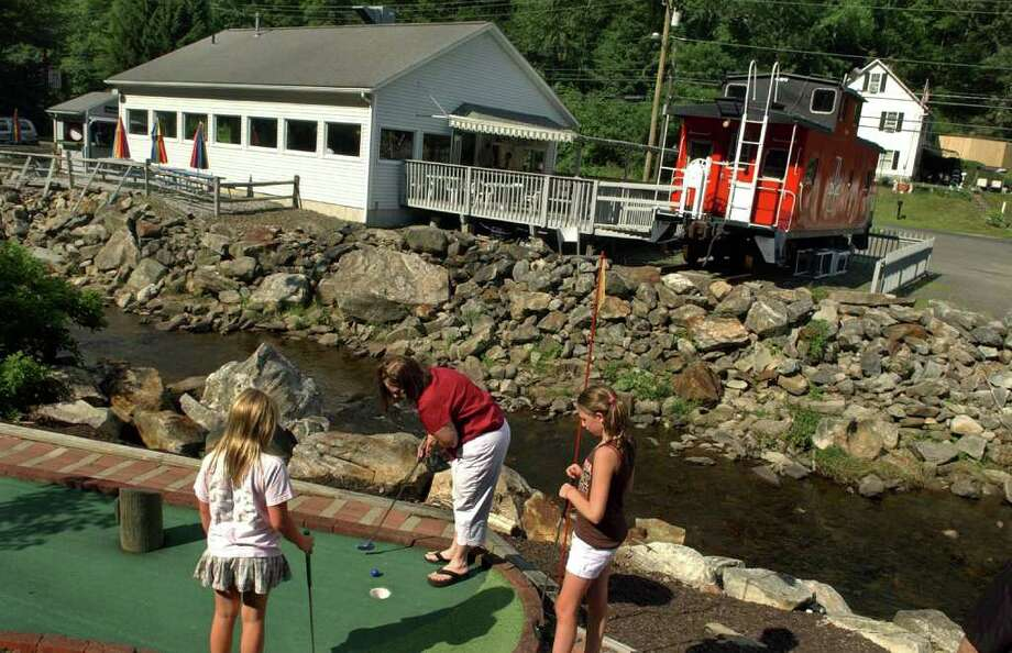 Lynda Chaco, of Seymour, plays a round of mini-golf with her gradaughters Lexi Robinson, 9, left, and Taylor, 12, while at the Old Saw Mill Grill and Miniature Golf Course in Oxford, Conn. on Friday July 15, 2011. Photo: Christian Abraham / Connecticut Post
