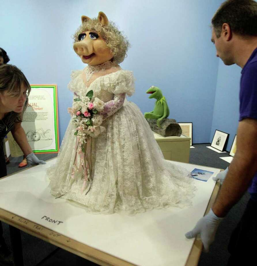 "Art handlers Jo Nigoghossia, left, and David Colosi, wheel in the Miss Piggy for the ""Jim Henson's Fantastic World"" exhibit, at the Museum of the Moving Image in New York in 2011. Photo: Richard Drew, AP / AP2011"