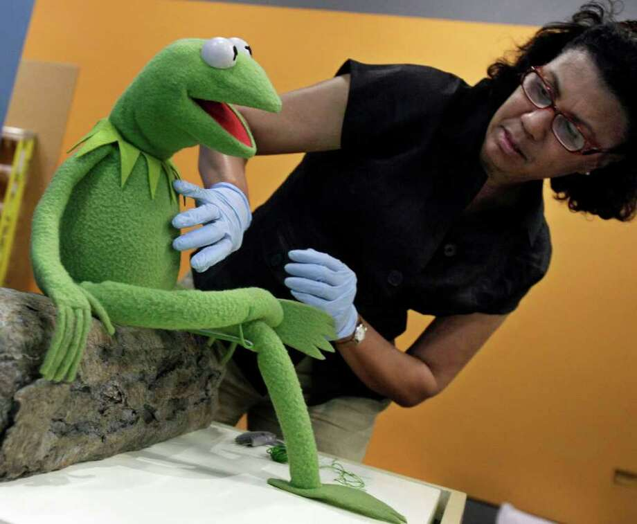 "Josette Cole, a registrar with the Smithsonian Traveling Exhibit Service, poses Kermit on his log for the ""Jim Henson's Fantastic World"" exhibit, at the Museum of the Moving Image in New York in 2011. Photo: Richard Drew, AP / AP2011"