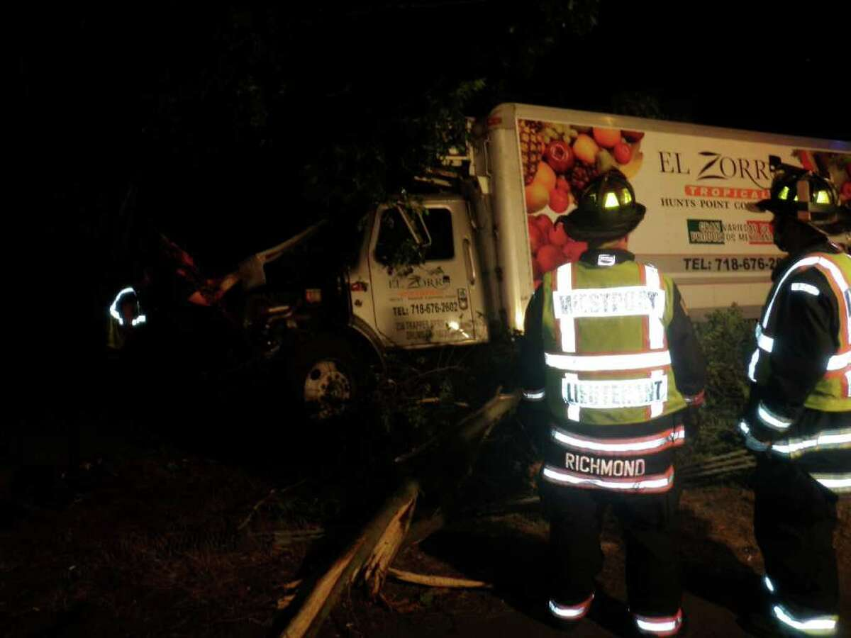 Firefighters inspect damaged box truck the crashed into trees off Interstate 95 in Westport Friday night.