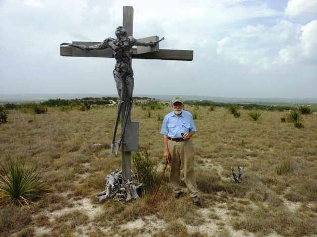 "Artist Phil Evett stands beside his 1962 work ""Crucifix"" atop a plateau at his Blanco home. Photos by Steve Bennett/sbennett@express-news.net"