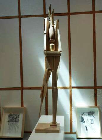 "Afternoon light falls across a Phil Evett wood sculpture titled ""Prosthesis"" in his gallery at his Blanco home."