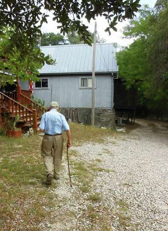 Phil Evett walks back toward his home on 20 acres in Blanco.