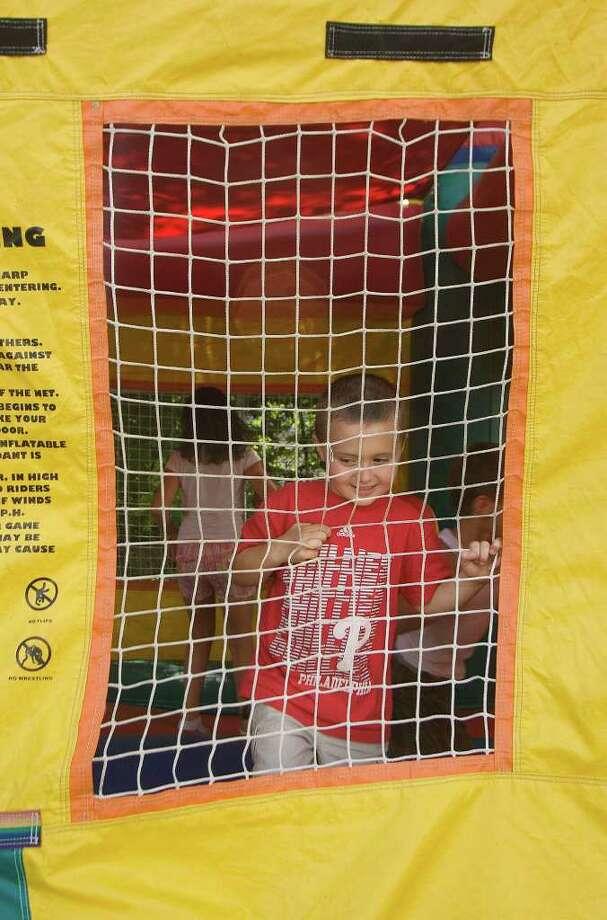 Caden Vickers, 4, of Danbury, enjoys the bouncy castle at the Jericho Partnership Block Party and Hawaiian Luau on Rose Street in Danbury on July, 16, 2011. Photo: Jason Rearick
