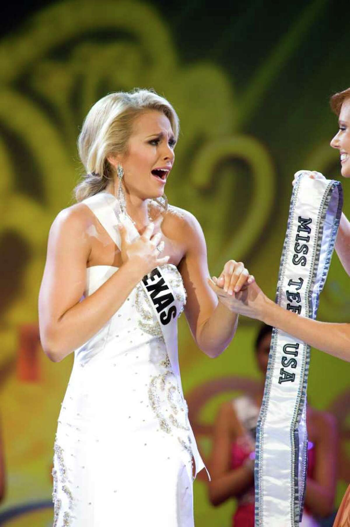 Miss Texas Teen USA 2011, Danielle Doty, prepares to receive the Miss Teen USA sash from Miss USA Alyssa Campanella.