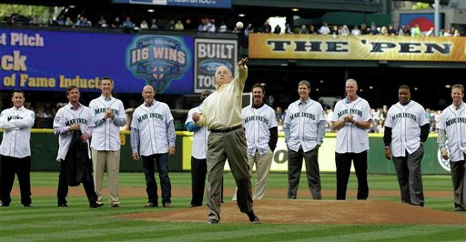 Former Seattle Mariners general manager Pat Gillick, center, is surrounded by players and coaches from the Mariners 116-win 2001 season as he throws out the first pitch of a baseball game against the Texas Rangers, Saturday, July 16, 2011, in Seattle. The group was present for a recognition of the 10th anniversary of the Mariners' 2001 season. (AP Photo/Ted S. Warren) Photo: Ted S. Warren, Associated Press / AP