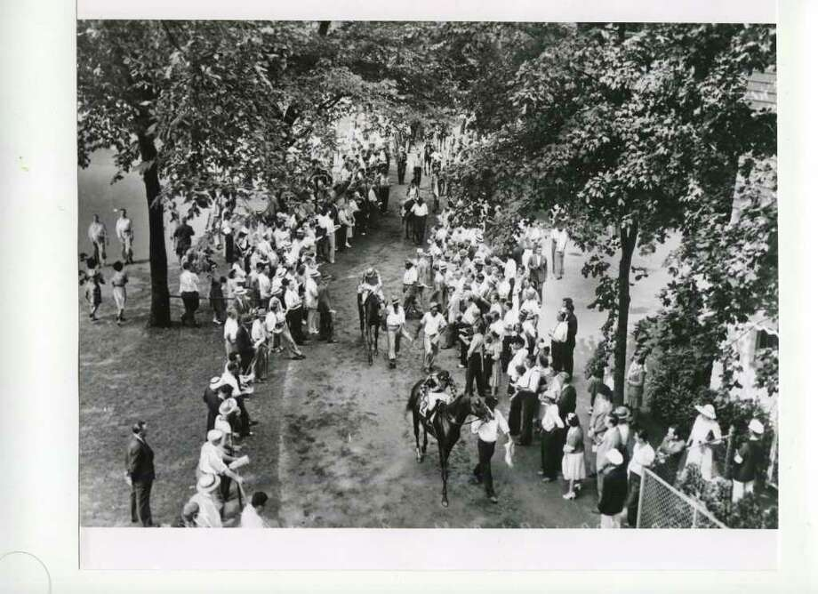 Horses and riders make their way to the track from the paddock, date unknown. The average fan could really get up and close and personal with the thoroughbreds back then. (Courtesy of Saratoga Springs Historical Museum, George S. Bolster collection)