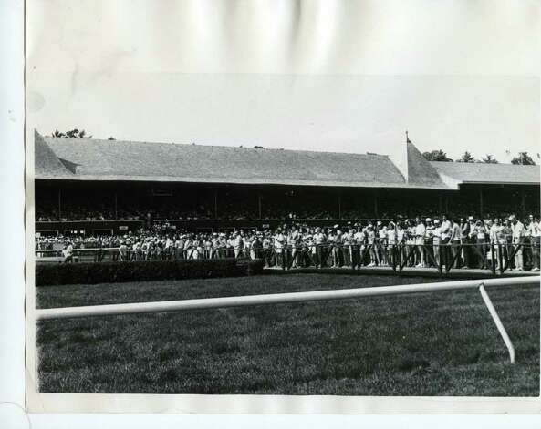 A crowd of people get ready to leave the Saratoga infield and return to the clubhouse and grandstand. Fans had to wait between races to make the trek back and forth from the infield. This photo is not dated. (Times Union Archives)