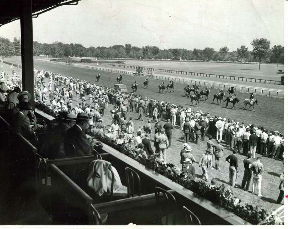 A field of horses head to the post on Aug. 1, 1939. Notice how well dressed most of the people are. Also, notice how the track's apron was grass way back when. (Times Union Archives)