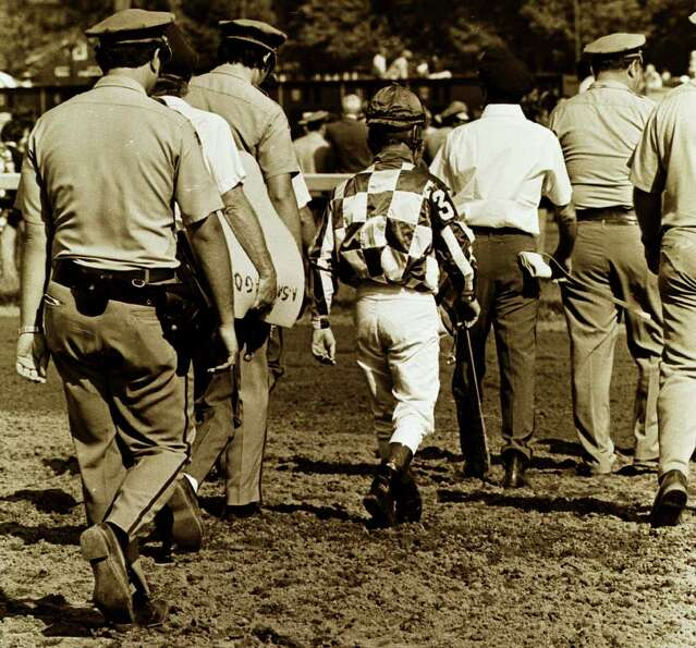 Times Union staff photo by Skip Dickstein -- Jockey Ron Turcott walks to the infield of the Saratoga