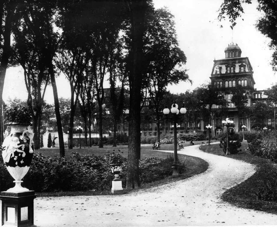 Photo Courtesy of the George S. Bolster Collection of the Historical Society of Saratoga Springs --  Photographer, H,B, Settle  --Congress Park looking west to the Grand Union Hotel in this 1916 photo. The vases are called 'Night' and 'Day' and are still in the park today (1999). The statue off to the left is 'The Spirit of Life'. It is a female angel with wings, built by Daniel Chester French, who also built the Lincoln Memorial. Photo: UNKNOWN / GEORGE S. BOLSTER COLLECTION