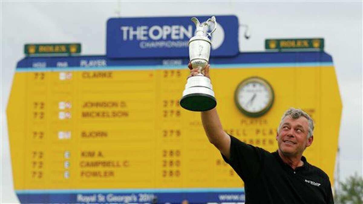 Northern Ireland's Darren Clarke holds up the Claret Jug trophy in front of the scoreboard on the 18th green as he celebrates winning the British Open Golf Championship at Royal St George's golf course Sandwich, England, Sunday, July 17, 2011. (AP Photo/Peter Morrison)