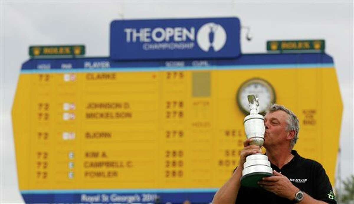 Northern Ireland's Darren Clarke kisses the Claret Jug trophy in front of the scoreboard on the 18th green as he celebrates winning the British Open Golf Championship at Royal St George's golf course Sandwich, England, Sunday, July 17, 2011. (AP Photo/Peter Morrison)