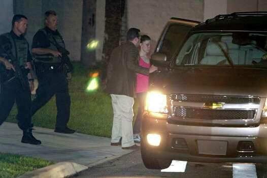 Casey Anthony, right, gets in an SUV with her lawyer Jose Baez, center, as she is escorted by Orange County Sheriff deputies after her release from the Orange County Jail in Orlando, Fla., early Sunday, July 17, 2011.  Anthony was acquitted last week of murder in the death of her daughter, Caylee. (AP Photo/John Raoux) Photo: John Raoux, STF / AP