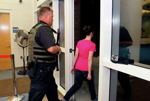 Casey Anthony, right, walks out of the Orange County Jail escorted by a sheriff's deputy  during her release in Orlando, Fla., early Sunday, July 17, 2011.  Anthony was acquitted last week of murder in the death of her daughter, Caylee. (AP Photo/Red Huber, Pool) Photo: Red Huber, POOL / Pool Orlando Sentinel