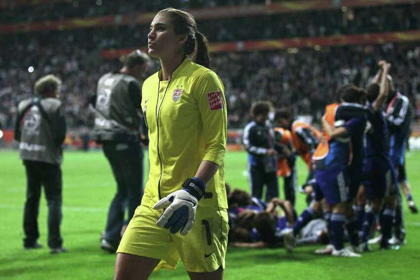 FRANKFURT AM MAIN, GERMANY - JULY 17: Japan celebrats winning the World Cup and Hope Solo of the USA looks dejected after losing 3-5 after penalty shoot-out the FIFA Women's World Cup Final match between Japan and USA at the FIFA World Cup stadium Frankfurt on July 17, 2011 in Frankfurt am Main, Germany. (Photo by Christof Koepsel/Getty Images)