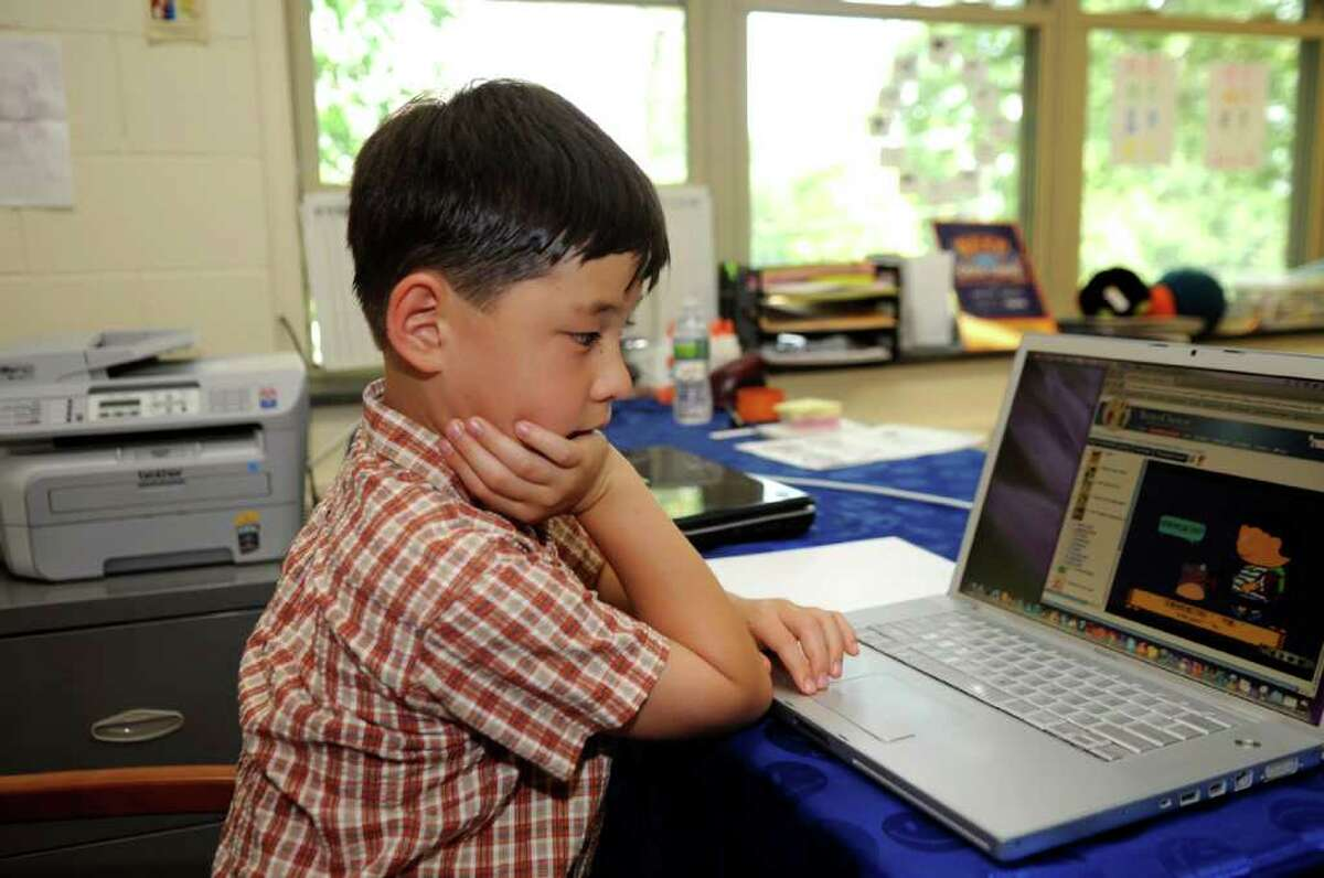 Madison Kung, 7, of Harrison, N.Y., a student of the Chinese Language School of Connecticut, works from a laptop at the Second Congregational Church in Greenwich Monday, July 11, 2011. The school recently introduced a new online tutoring program that allows students from all over Connecticut to take classes from home.