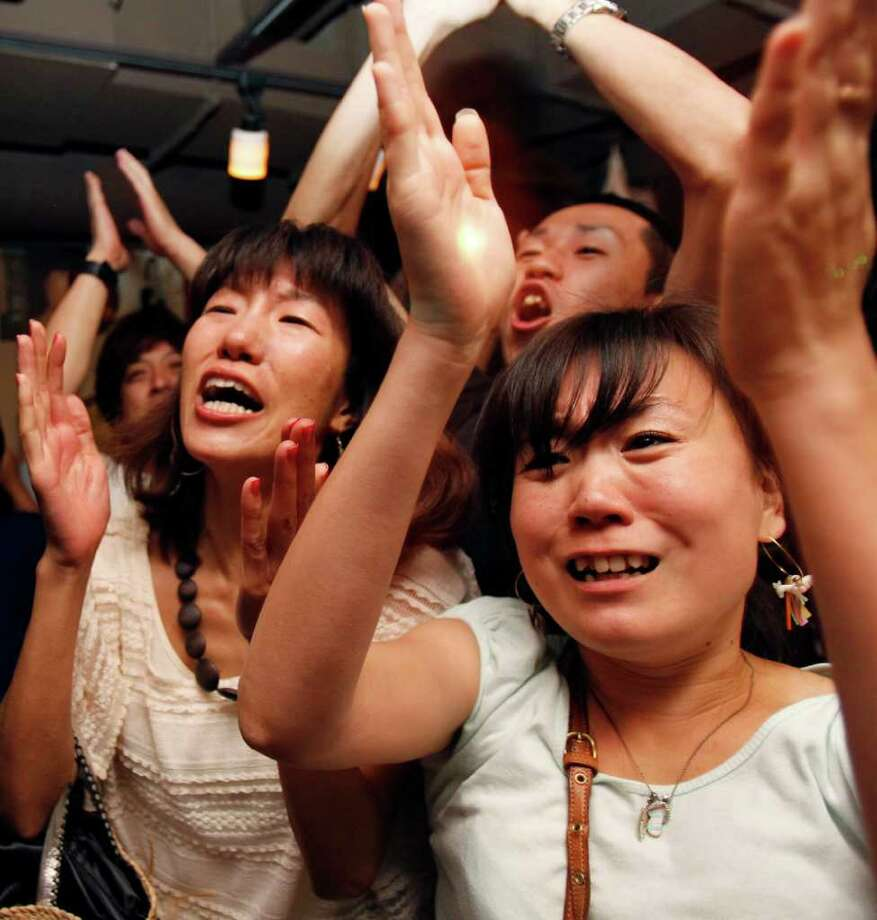 Japanese fans celebrate at a sports bar in Tokyo Monday morning, July 18, 2011 after Japan beat the United States in their final match at the Women?s Soccer World Cup in Frankfurt, Germany. (AP Photo/Koji Sasahara) Photo: Koji Sasahara, STF / AP