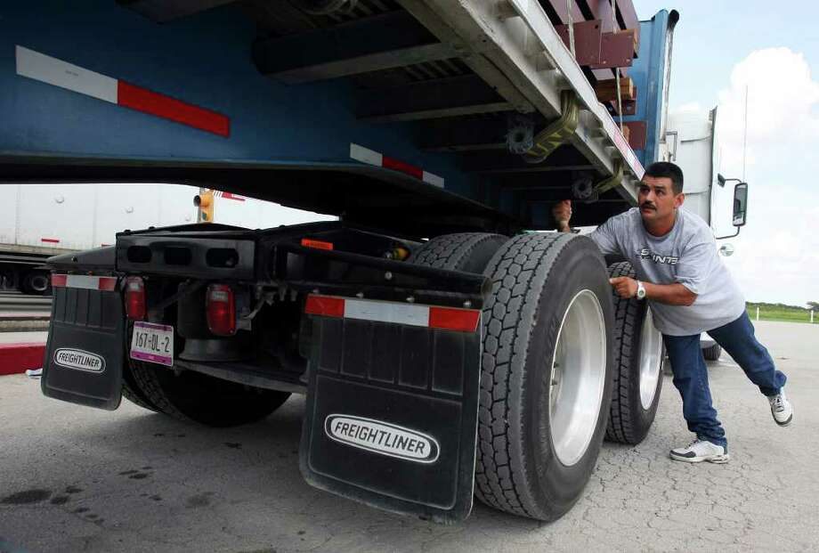 FOR METRO - Transportes Olympic driver Luis Gonzalez checks the tires on his semi after spending the night at a truck stop in San Antonio, Tx Saturday Sept. 8, 2007. (PHOTO BY EDWARD A. ORNELAS) Photo: EDWARD A. ORNELAS, STAFF / SAN ANTONIO EXPRESS-NEWS