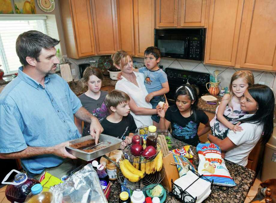 Columbian orphans join with the Evermon family in the home of Jeremy Evermon and Vanessa Evermon, 15115 Brown Road, Tomball, Texas. Fixing lunch L-R ID: Jeremy Evermon (dad); Emily Evermon, age 12 (in brown top); Wesley Evermon, age 10 (black top); Vanessa Evermon (mom) white shirt; holding Omar (one name), age 6 (gray shirt); Marian (one name), age 11 (black shirt, white headband); Savannah Evermon, age 4; being held by Katerin (one name), age 13. The Columbian orphans just arrived early this morning. NOTE: I wasn't allowed to shoot individual orphans or use their last names, so I was restricted to this group shot. Saturday, July 16, 2011. (Craig H. Hartley/Chronicle) Photo: Craig Hartley, Freelance / Copyright: Craig H. Hartley