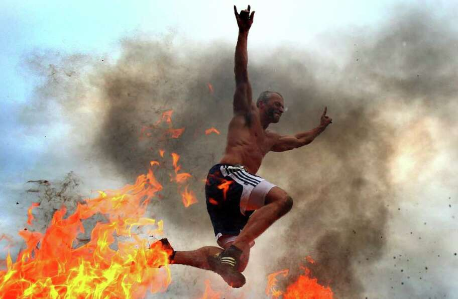 A participant leaps over fire during the inaugural Warrior Dash Washington on Sunday, July 17, 2011