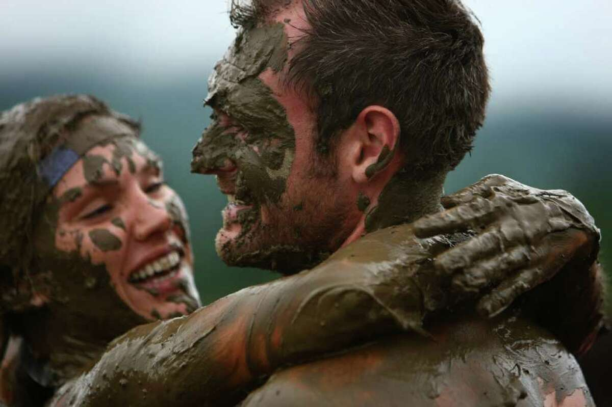 John Murray and his wife Stephanie of Gig Harbor embrace after completing the inaugural Warrior Dash Washington on Sunday, July 17, 2011 in North Bend. Approximately 23,000 people competed in the 3.55 mile course which included a mud pit and flaming obstacles.