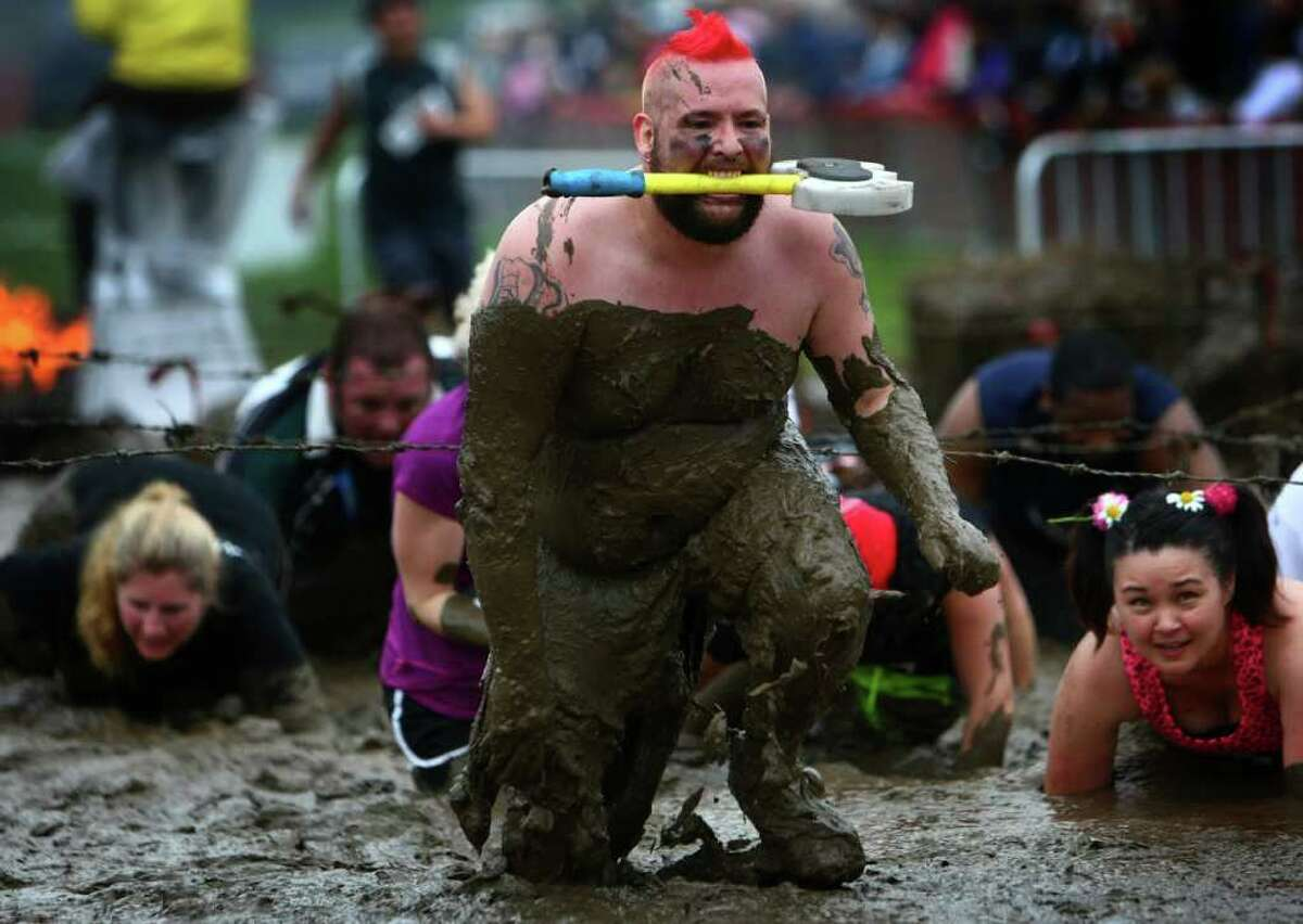 A participant slogs through mud during the inaugural Warrior Dash Washington in North Bend. Approximately 23,000 people competed in the 3.55 mile course which included a mud pit and flaming obstacles.