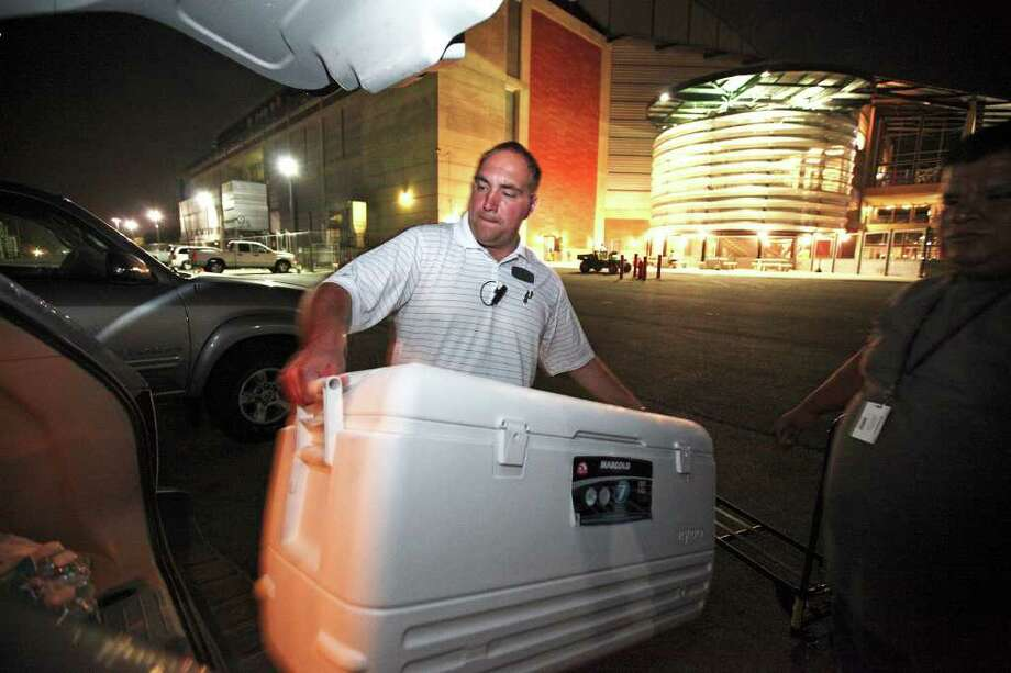 ARAMARK General Manager Tim Witkowski loads a cooler of unsold hot dogs and pretzels into Michael Martinez's car at the AT&T Center so the food can be donated to Haven for Hope. Photo: Andrew Buckley/abuckley@express-news.net / Copyright: Andrew Buckley