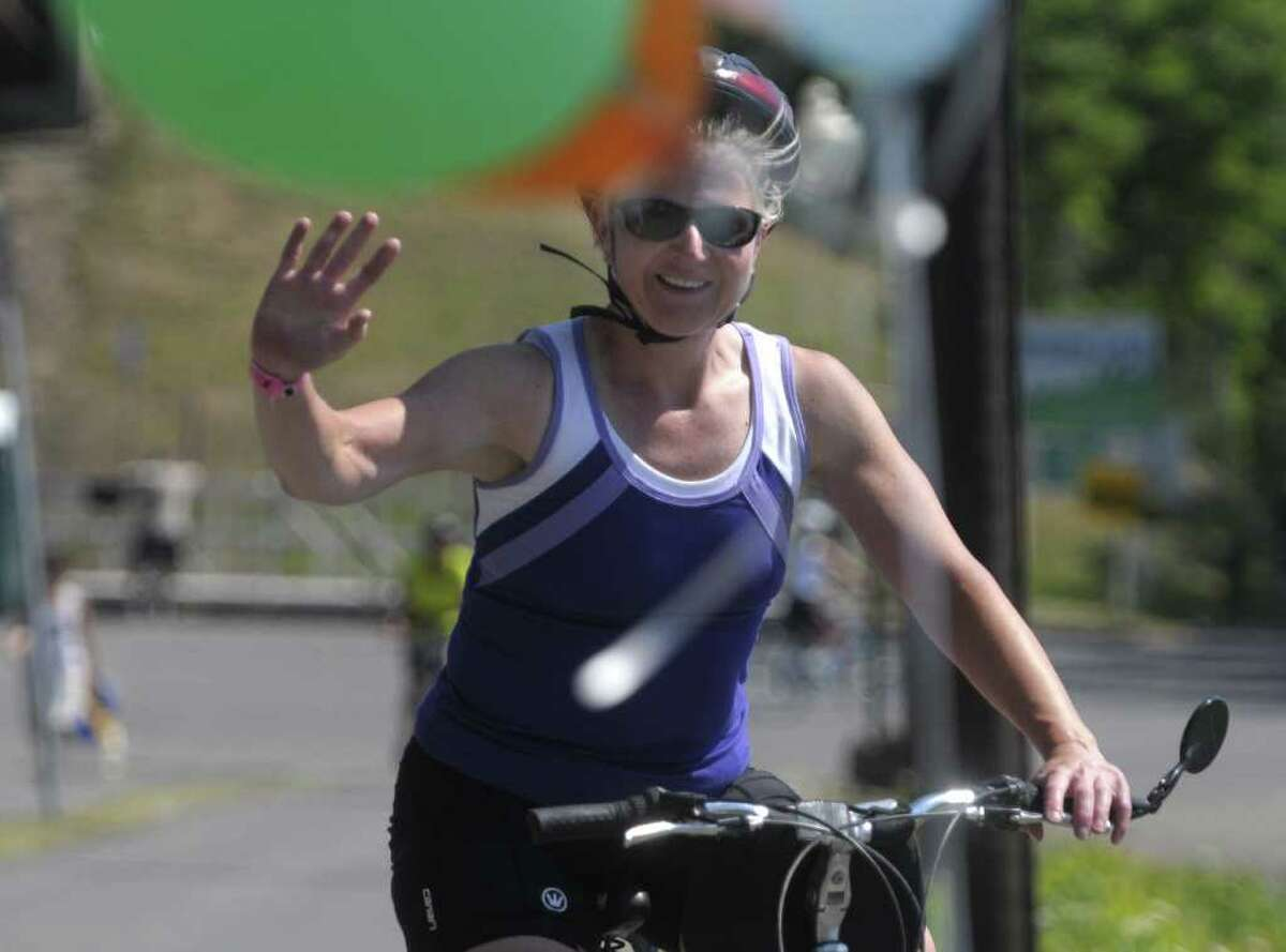 Cyclist Kelly Belenchia from Voorheesville waves to friends as she crosses the finish line at the Corning Preserve where riders taking part in the 13th annual Cycling the Erie Canal tour ended their eight day ride on Sunday, July 17, 2011 in Albany. Some 500 bicyclists from 35 states took part in the tour this year. The 400-mile bicycle tour began last Sunday in Buffalo. (Paul Buckowski / Times Union)