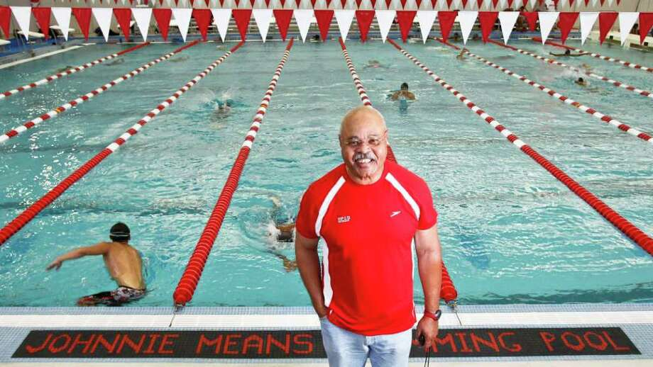 Johnnie Means stands in front of a sign dedicating the pool in his honor at the Harris County Aquatic Program, Wednesday, June 29, 2011, in Houston.  Means is the director and swimming coach for the Harris County Aquatic Program. He was instrumental in building the facility three years ago, thanks to the help of Commissioner Franco Lee and together, they raised $8 million to build the facility. Means contributed his own money to the program as well. Means and Lee wanted to create a program, where children didn't have to pay to learn how to swim.   Means started teaching kids how to swim competitively back in the early 60s. He was part of one of the first predominately black swim teams in the nation, when he attended TSU.    ( Michael Paulsen / Houston Chronicle ) Photo: Michael Paulsen, Staff / © 2011 Houston Chronicle