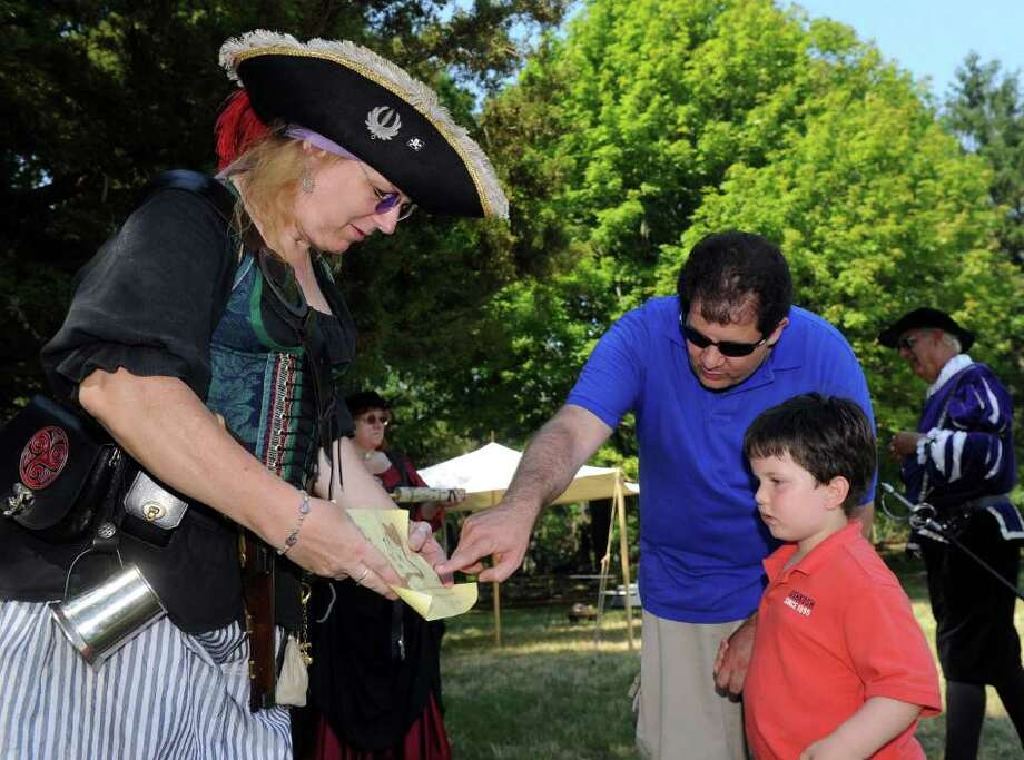 Rachelle Hayes, a pirate volunteer, shows Alex Arpino, 4, and his father, Greg, a treasure map during the Norwalk Seaport Association's Pirate Adventure on Sheffield Island on Saturday, July 16, 2011. Photo: Lindsay Niegelberg / Connecticut Post