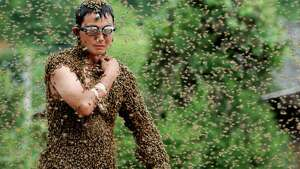 SHAOYANG, CHINA - JULY 16:  (CHINA OUT)  Bees cover beekeeper Wang Dalin during a 'bee bearding' contest on July 16, 2011 in Shaoyang, Hunan Province of China. Wang Dalin won the contest against fellow beekeeper Lu Kongjiang after attracting 26.86kg of bees onto his body, covered only by a pair of shorts and swimming goggles.