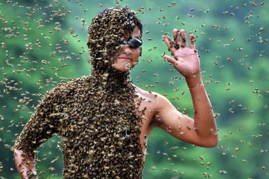 In this photo released by Xinhua News Agency, 20-year-old beekeeper Lu Kongjiang waves as bees cover his body during a contest against 42-year-old Wang Dalin, also a beekeeper, in Longhui County of Shaoyang City, central China's Hunan Province, Sunday, July 17, 2011. Wang finally won in the hour-long duel since 26 kilograms (57 pounds) of bees covered his body, Xinhua said. (AP Photo/Xinhua/Lu Jianshe) NO SALES Photo: AP