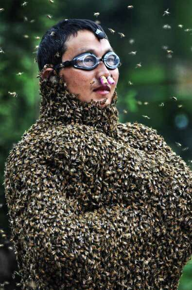 In this photo released by Xinhua News Agency, 42-year-old beekeeper Wang Dalin is covered with bees