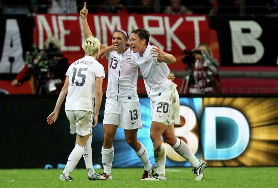 United States' Alex Morgan, center, celebrate with United States' Abby Wambach and United States' Megan Rapinoe, left, scoring the opening goal during the final match between Japan and the United States at the Women?s Soccer World Cup in Frankfurt, Germany, Sunday, July 17, 2011. (AP Photo/Michael Probst) Photo: Michael Probst, STF / AP