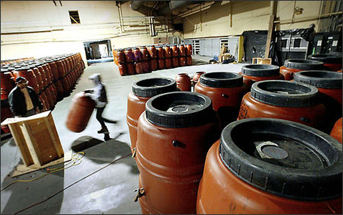 Workers from the Seattle Conservation Corps construct rain barrels in the old Navy commissary at Sand Point's Magnuson Park in the photo originally published April 3, 2003. (Photo by Dan DeLong/Seattle Post-Intelligencer).