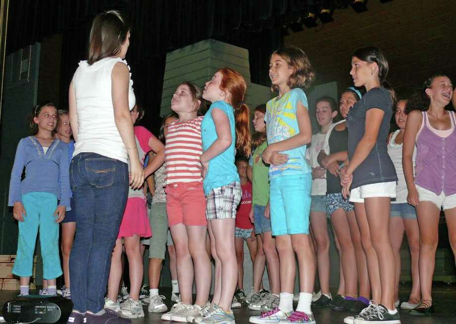 Counselor Julianne Shea takes campers in the Parks & Recreation Department's Pre-teen Theatre through some warm up exercises on the stage at Fairfield Warde High School. Photo: Genevieve Reilly / Fairfield Citizen