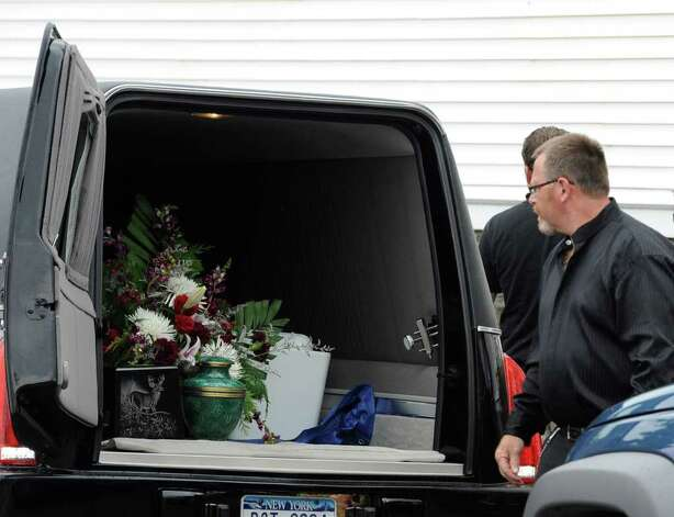Two urns sit in the hearse as mourners leave the Cambridge United Presbyterian Church in Cambridge, N.Y. July 18, 2011, after the funeral of Dan Harrington, Deputy Town Highway Superintendent for the Town of White Creek, his wife Lisa Harrington and step son Josh O'Brien who were shot to death and their bodies burned allegedly by their son Mathew Slocum.  (Skip Dickstein / Times Union) Photo: SKIP DICKSTEIN / 2011